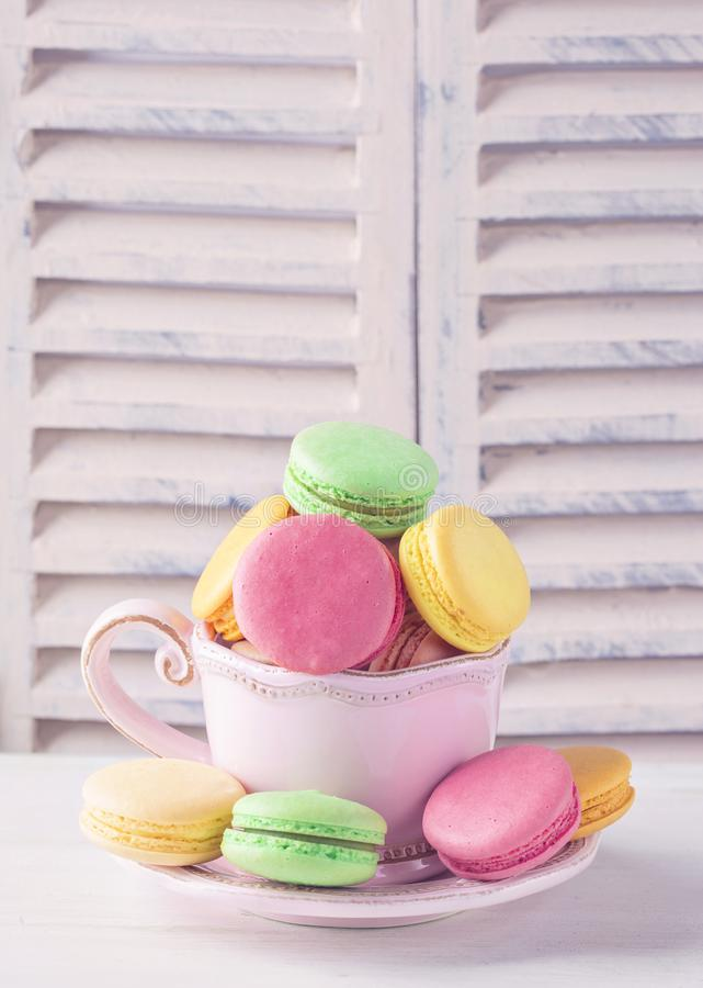 Colorful macarons in a cup royalty free stock photos