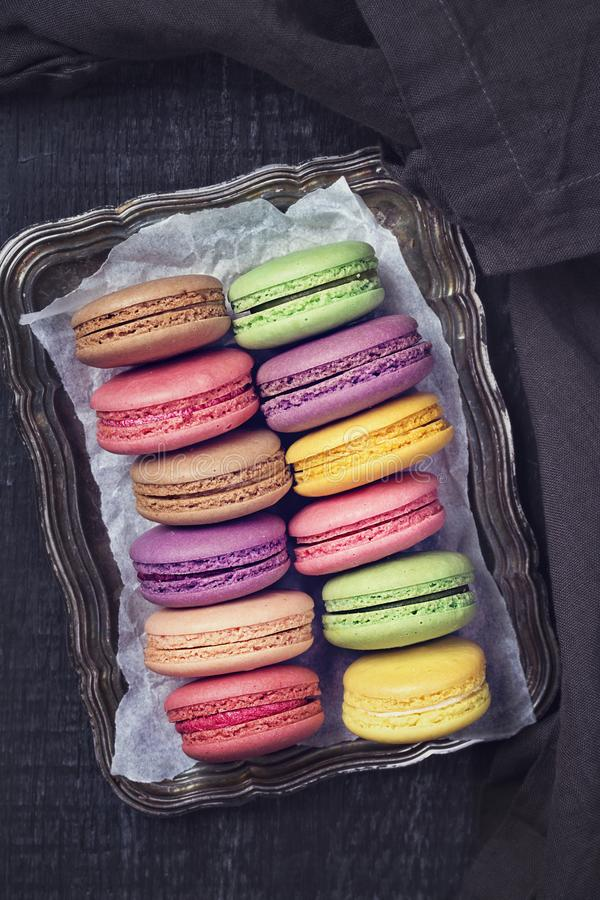 Colorful macarons. On a dark wooden background royalty free stock image