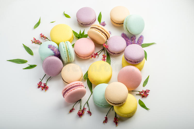 Colorful macarons with leaves and red flowers on a white background. French delicate dessert stock photos