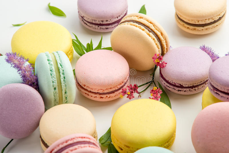Colorful macarons with leaves and red flowers on a white background. French delicate dessert royalty free stock image