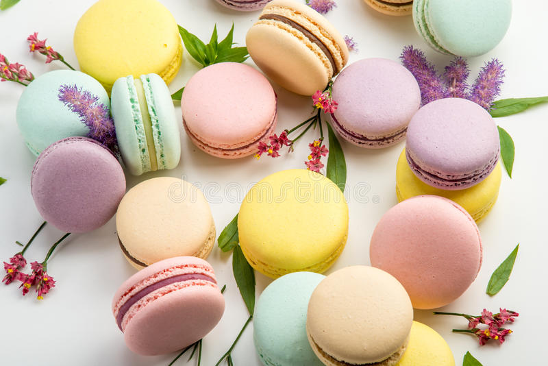 Colorful macarons with leaves and red flowers on a white background. French delicate dessert stock images