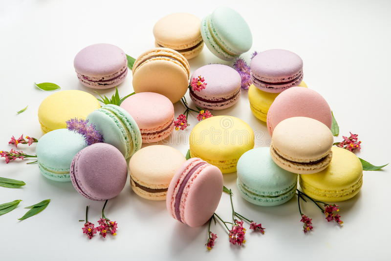 Colorful macarons with leaves and red flowers on a white background. French delicate dessert stock photo