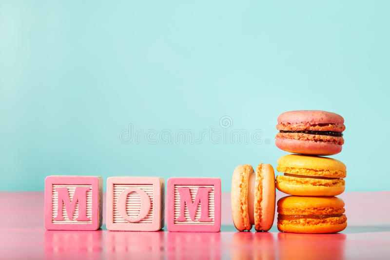 Colorful macarons with mom wood blocks on bright pastel background. Colorful macarons with mom wood blocks for mothers day on bright pastel background royalty free stock photo