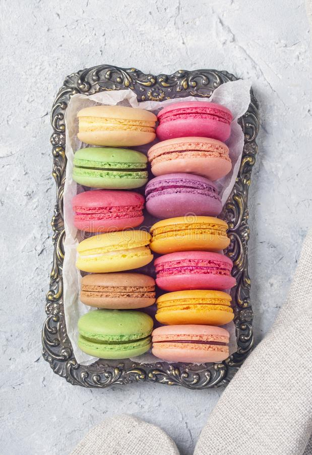 Colorful macarons on a plate. On a grey  background royalty free stock images