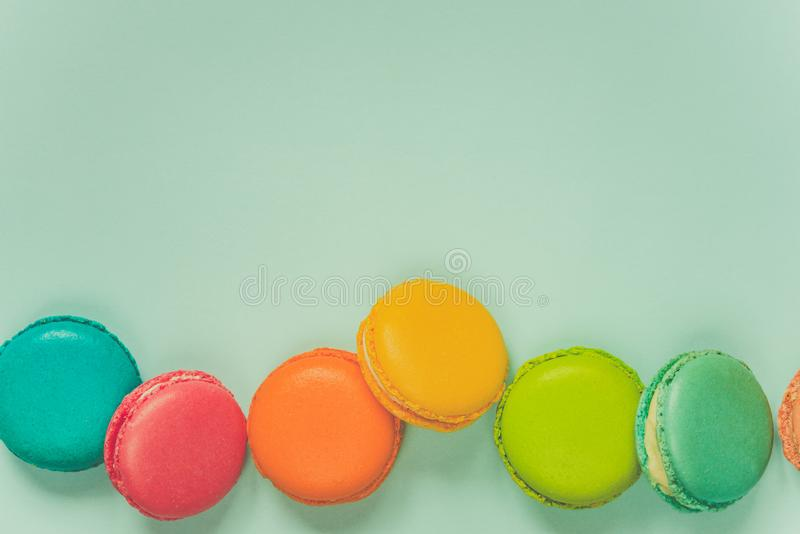 Colorful macaroons arranged over blue background. Copy space. Vintage effect. stock photos