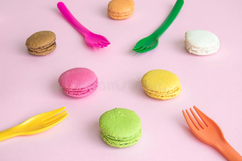 Multicolored macaroons and disposable forks on table abstract stock photos