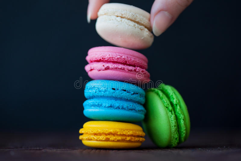 Colorful macaroons tower close-up on black background. Female hand takes one cookie stock photo