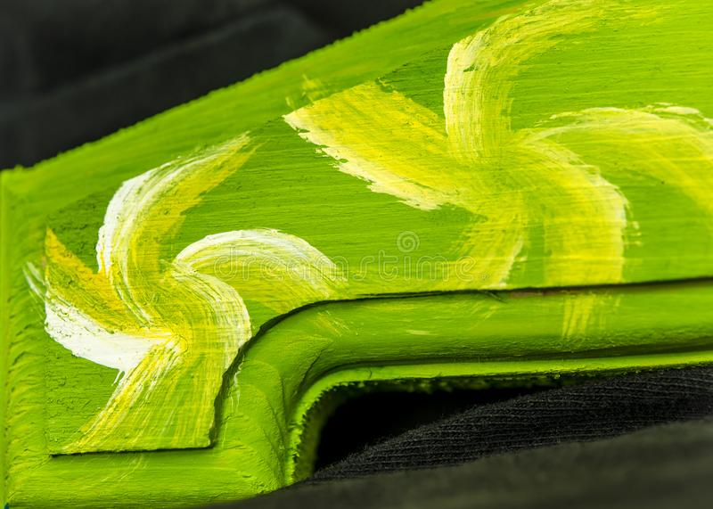 Colorful macro abstract with yellow, lime and white swirls painted on bright green wooden texture royalty free stock photography