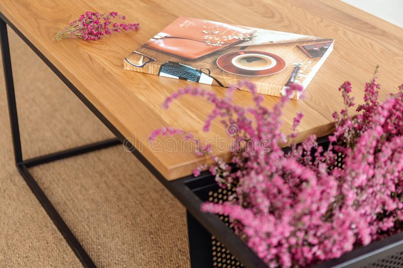 Colorful magazine on the wooden table in stylish living room of modern apartment. Colorful magazine and heather on the wooden table in stylish living room of royalty free stock image