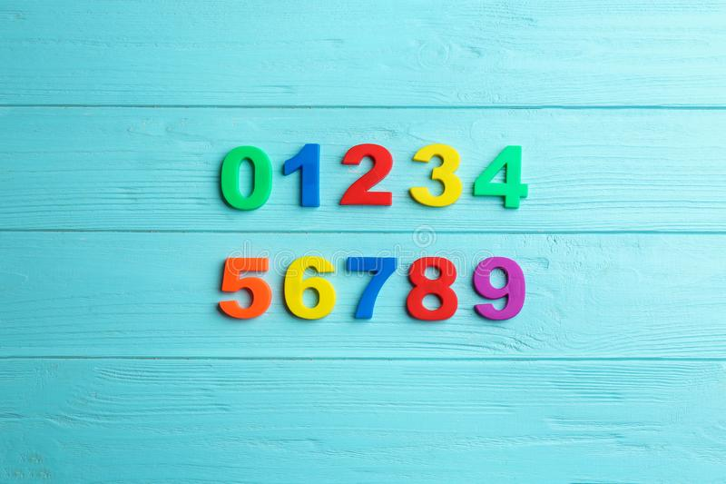 Colorful magnetic numbers on blue wooden background, flat lay royalty free stock photography