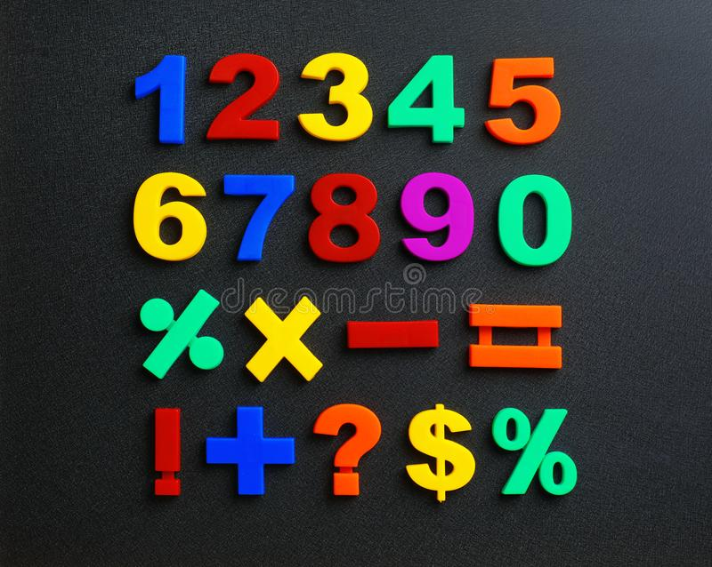 Colorful magnetic numbers and math symbols on black background royalty free stock photo
