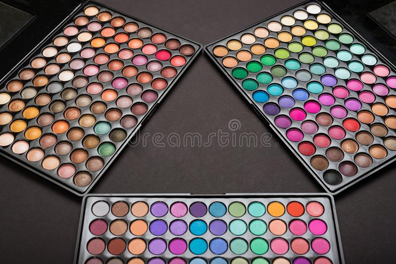 Colorful make-up eyeshadow palettes arranged as triangle on black. Background stock photo