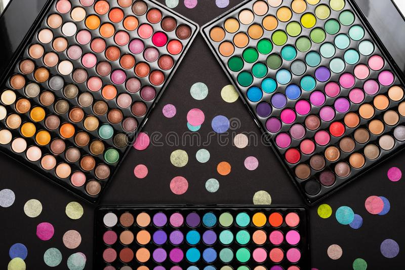 Colorful make-up palettes and colorful confetti on black background. Make-up concept. Top view stock photography