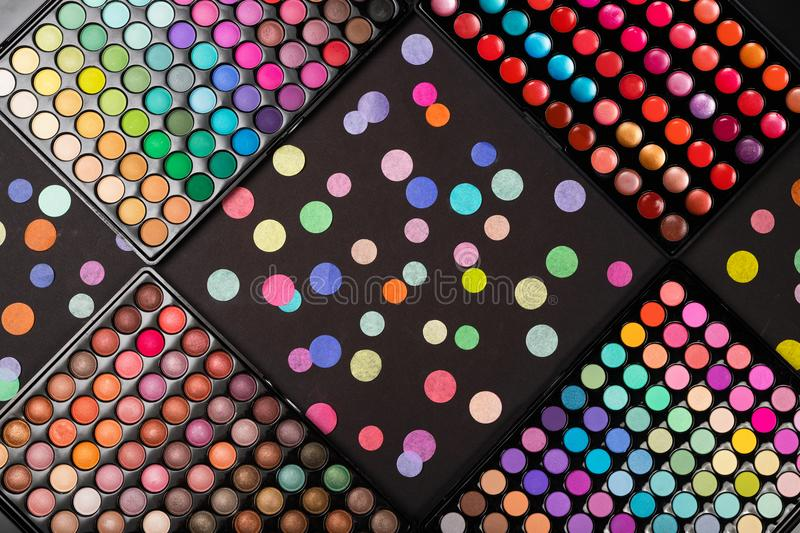 Colorful make-up palettes and colorful confetti on black background. Colorful make-up palettes and scattered colorful confetti on black background. View from stock photography