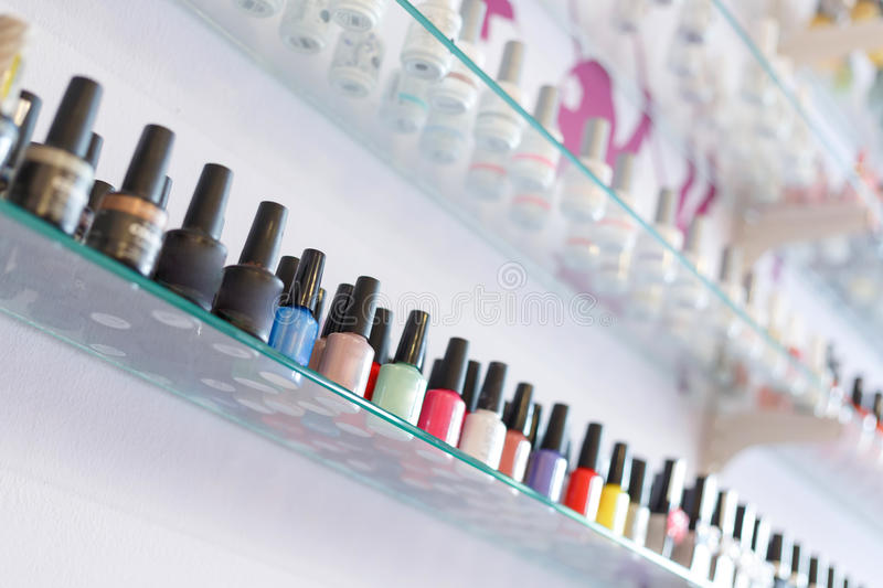Colorful manicure nail polish bottle collection set on shelf. Fashion colorful manicure nail polish bottle collection set on glass display shelf, blur interior stock images