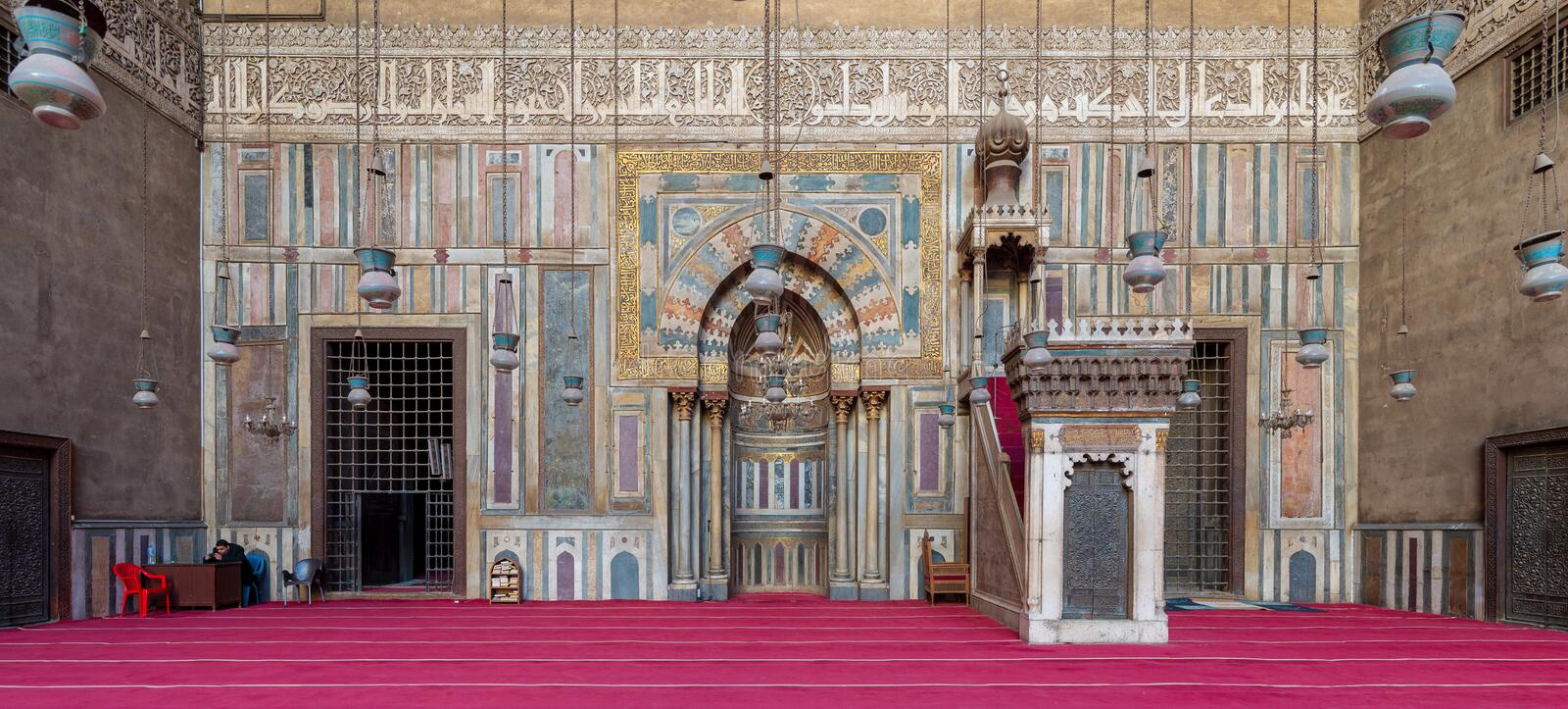 Colorful marble wall with engraved Mihrab niche and wooden Minbar Platform at the Mosque of Sultan Hassan, Cairo, Egypt royalty free stock image