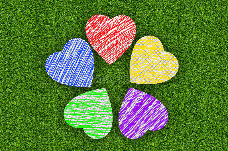 Colorful marker drawing hearts over green grass stock photography