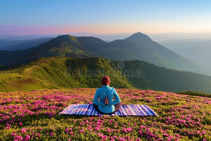 Colorful mat. The yoga girl in the lotus pose. The lawn with the rhododendron flowers. High mountains. Magical forest. Summer. stock photo