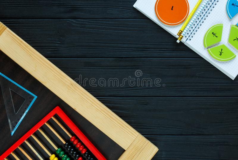 Colorful math fractions on dark wooden background or table. Interesting math for kids. Education, back to school concept. Geometry stock photography