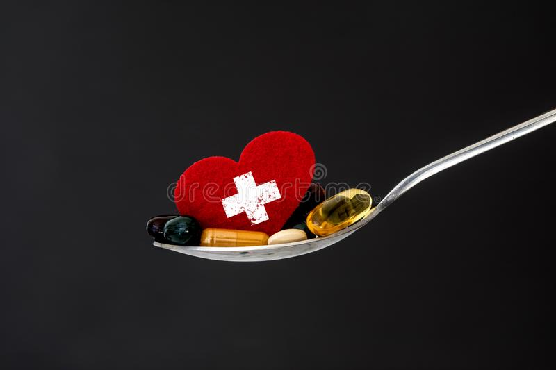 The colorful medical supplement and drug pills with red heart in spoon , pharmaceutical cardiology drugs for heart health care. Colorful medical supplement and royalty free stock photo