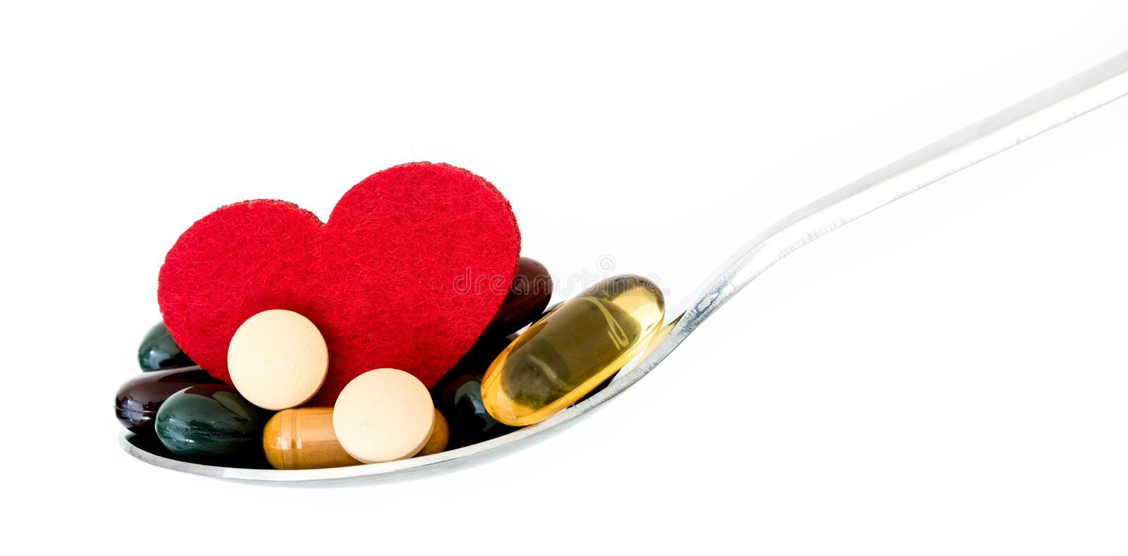 The colorful medical supplement and drug pills with red heart in spoon , pharmaceutical cardiology drugs for heart health care. Colorful medical supplement and stock photos