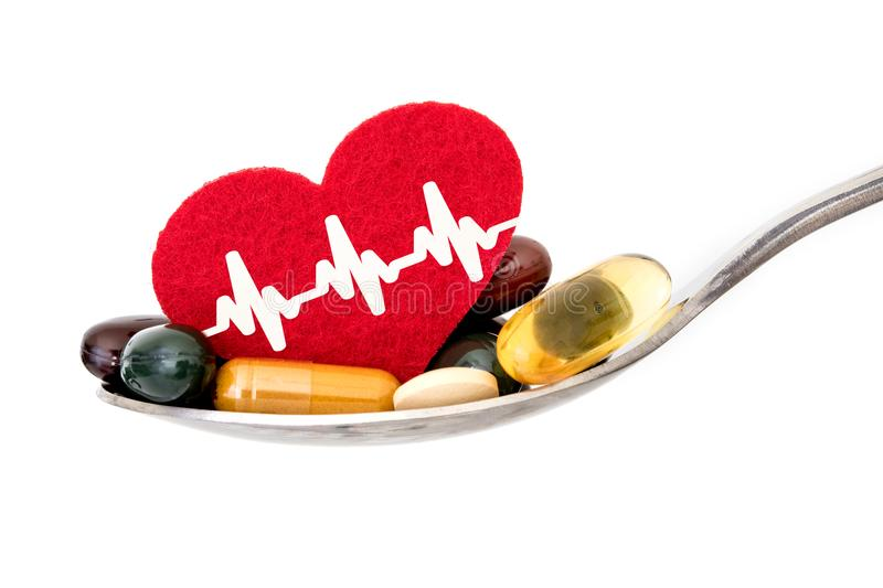Colorful medical supplement and drug pills with red heart in spoon , pharmaceutical cardiology drugs for a heart health care dis. Colorful medical supplement and stock image