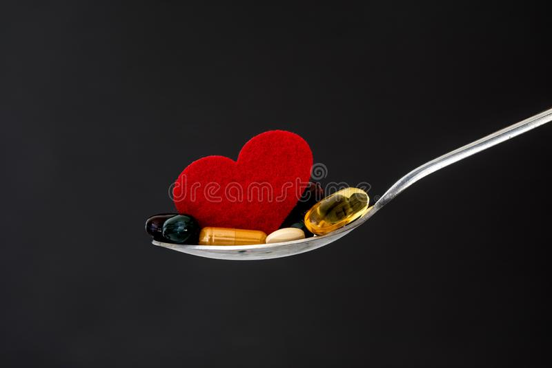 The colorful medical supplement and drug pills with red heart in spoon , pharmaceutical cardiology drugs for heart health care. Colorful medical supplement and royalty free stock images