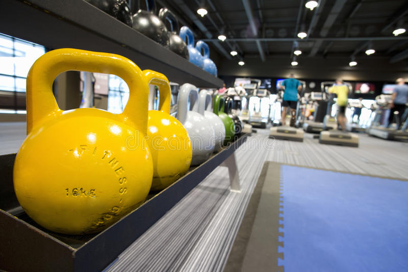 Colorful medicine balls on rack in health club and people exercising in background royalty free stock photo