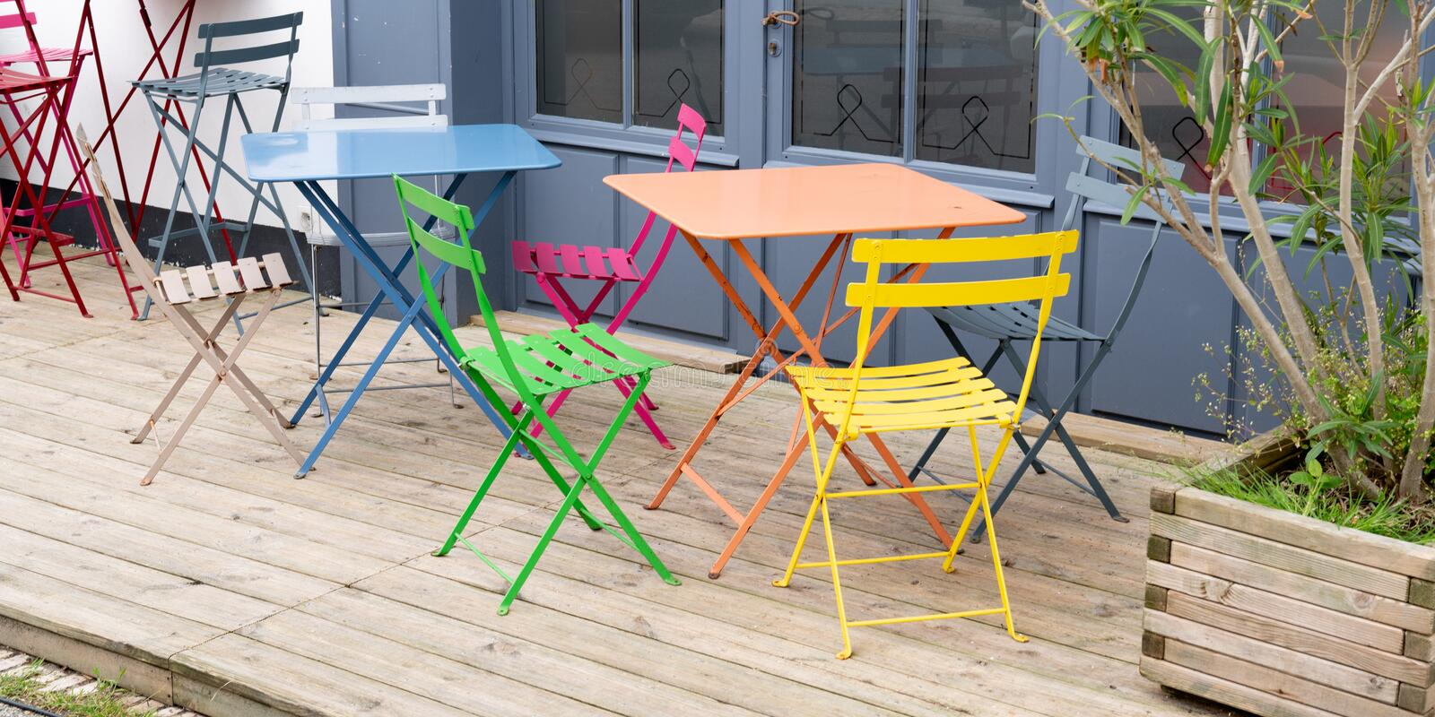 Colorful metal chairs and table on empty terrace at cafe in web banner template royalty free stock image