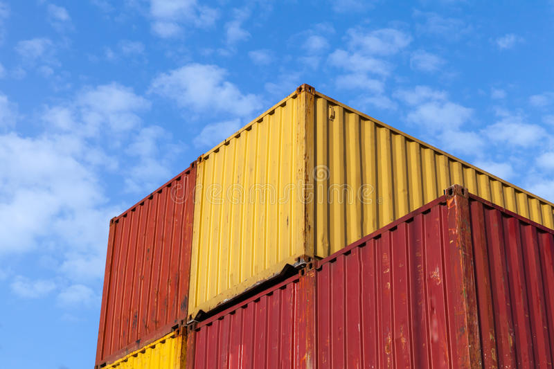 Colorful metal Industrial cargo containers. Are stacked under blue cloudy sky stock image