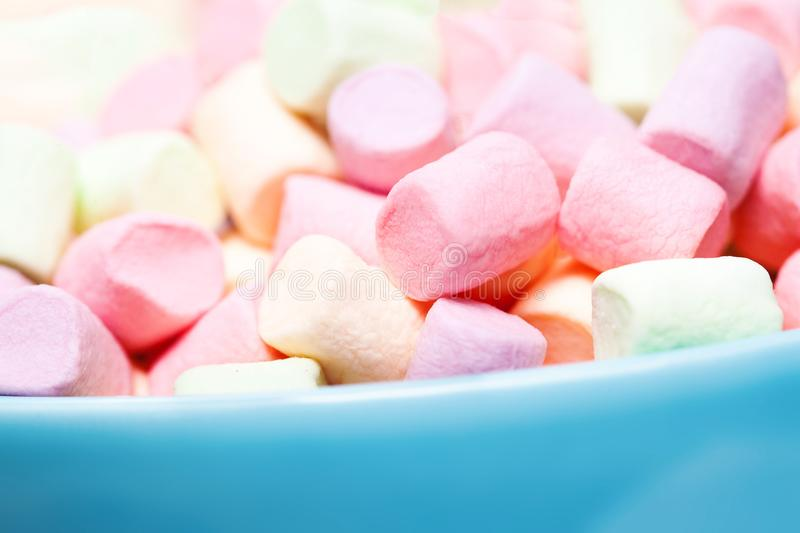 Colorful mini marshmallows in a blue bowl as background, macro. stock photo