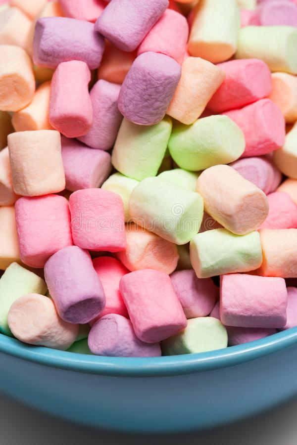Colorful mini marshmallows in a blue bowl as background, macro. stock image