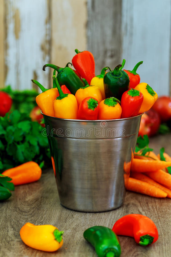 Colorful mini sweet peppers vintage metal pail wood background stock photos