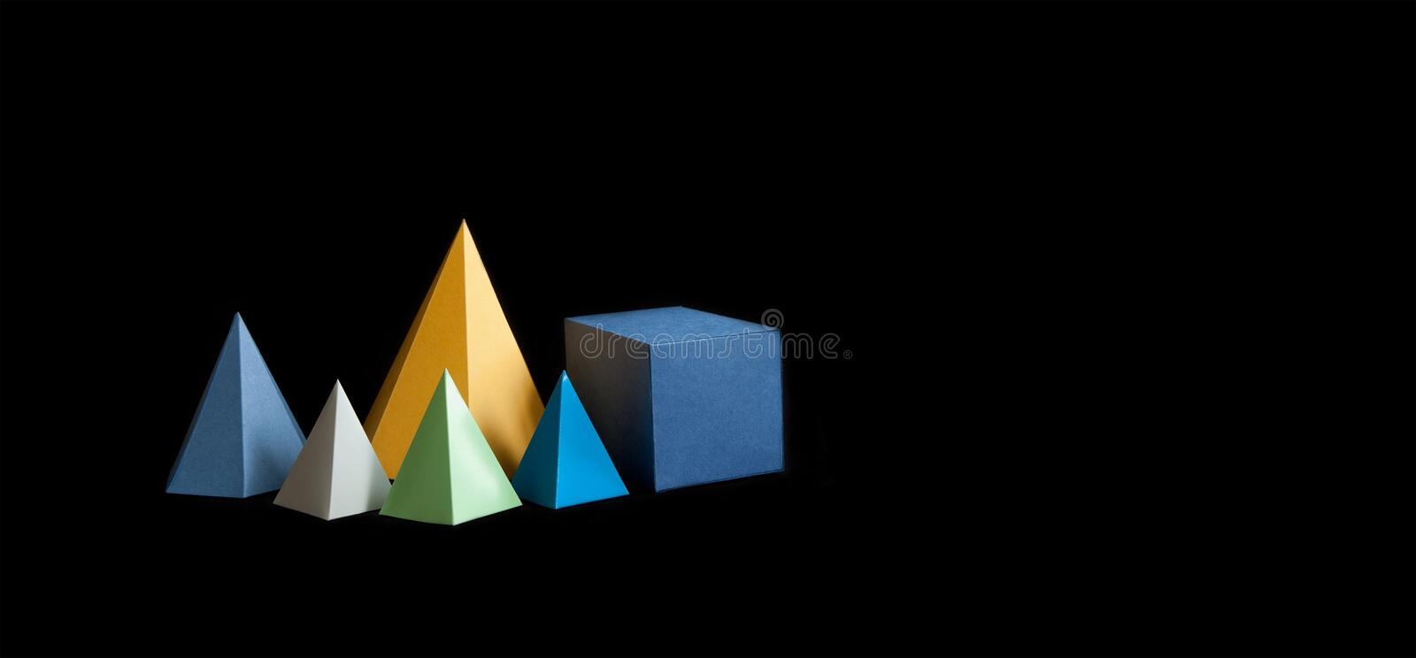Colorful minimalistic composition abstract geometric solid figures on black background. Pyramid prism rectangular cube. Yellow blue pink green colored figures stock photography