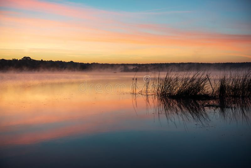 colorful misty sunset on the river in summer stock photo