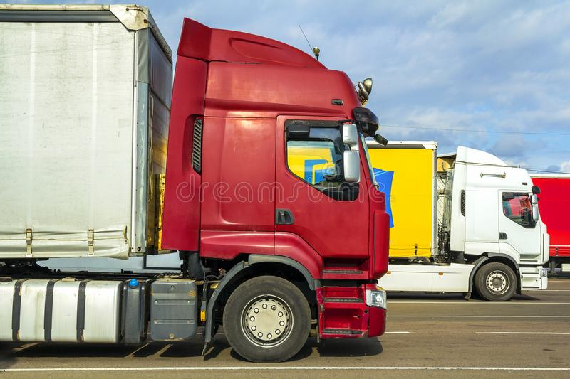 Colorful modern big semi-trucks and trailers of different makes stock photos