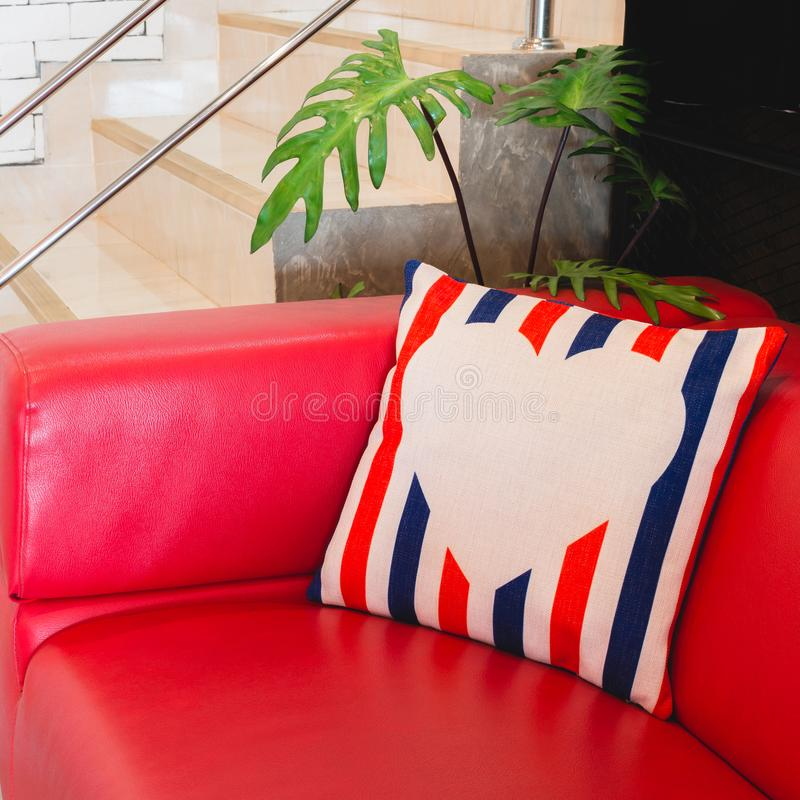 Colorful modern design pillow put on red luxury sofa. Beautiful decoration house object of relax or rest royalty free stock photography