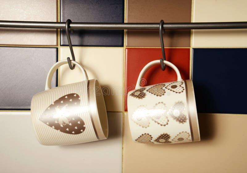 Colorful mugs on hooks. Tile background stock photos