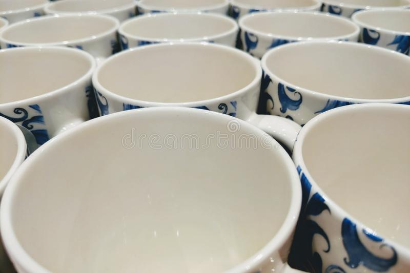 Colorful mugs on shelf in retailer gift shop.  royalty free stock photography