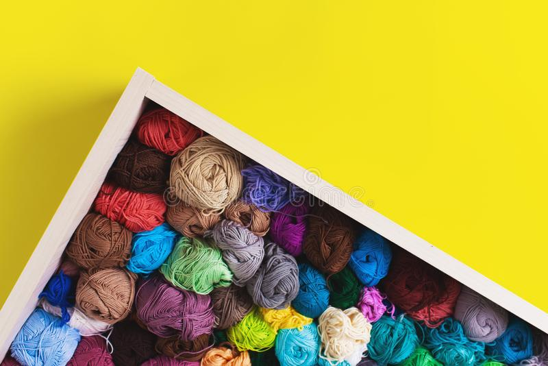 Colorful multicolored skeins. Crocheting and knitting. Colorful multicolored skeins of yarn in the box on yellow background. Women`s hobby. Banner royalty free stock images