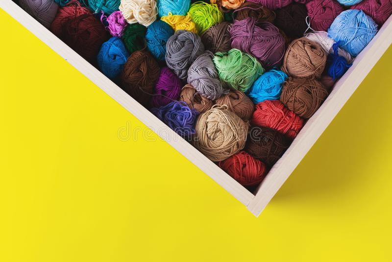 Colorful multicolored skeins. Crocheting and knitting. Colorful multicolored skeins of yarn in the box on yellow background. Women`s hobby. Banner stock images