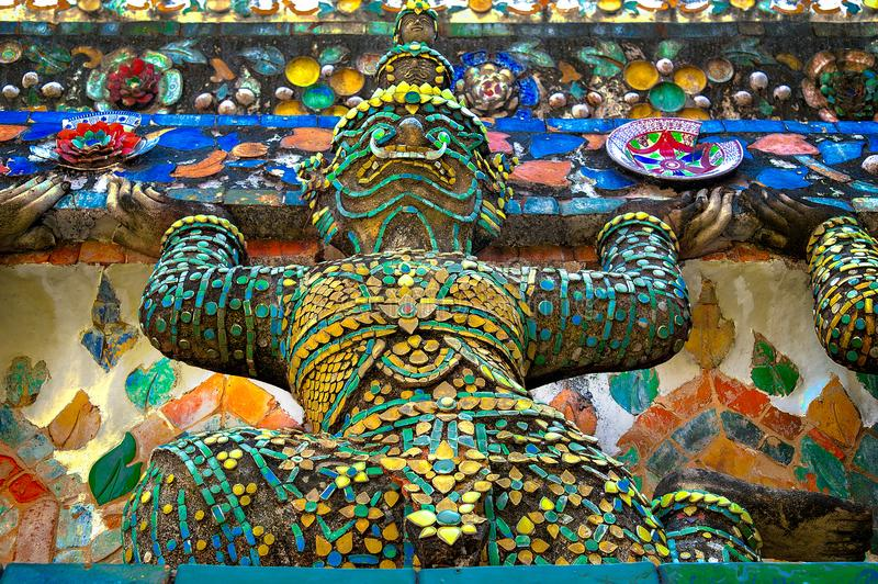 COLORFUL MYSTICAL GIANT STATUE. Mystical giant statues decorated with pieces of various shapes and sizes of ceramic tiles. They are set to stand guarding and stock photos