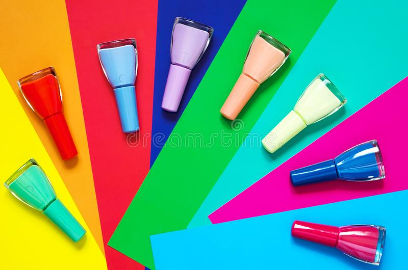 Colorful nails polish bottles on multi colored paper. The concept of fashion and beauty industry. stock images