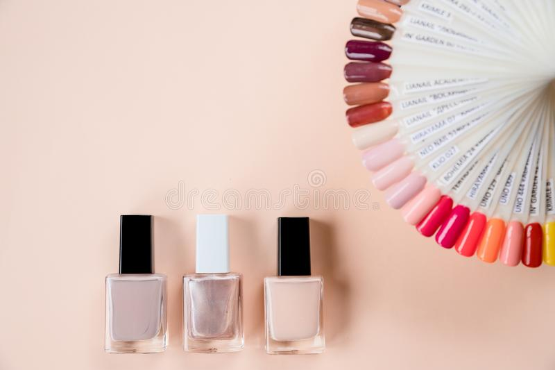 Colorful nails polish palette for manicure on pastel background. Collection of nails color polish samples, top view. Colorful nails polish palette for manicure stock images