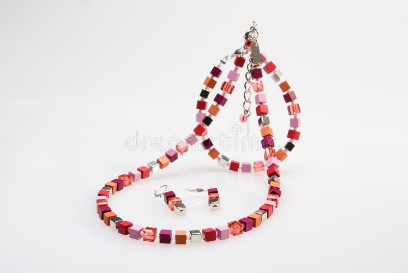 Colorful necklace, bracelet and earrings. On white background royalty free stock photo