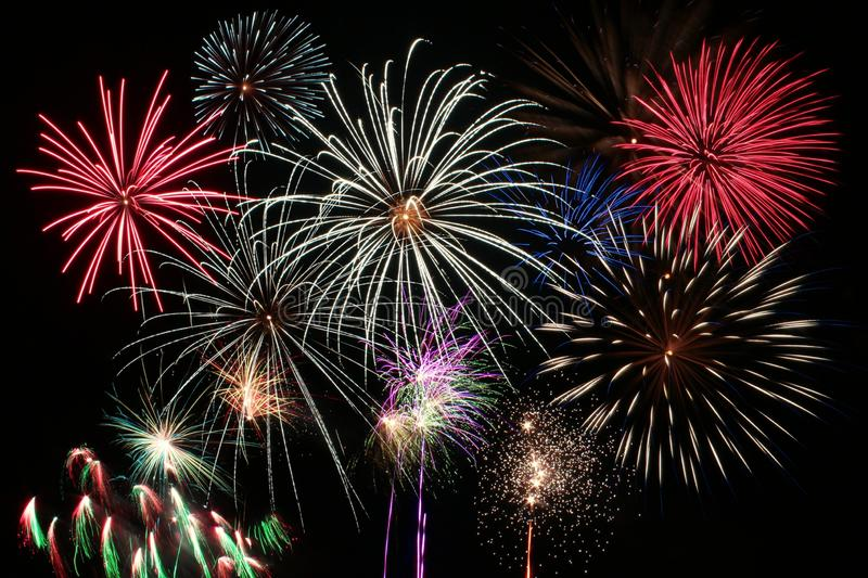 Colorful new-year fireworks on black background at night royalty free stock images