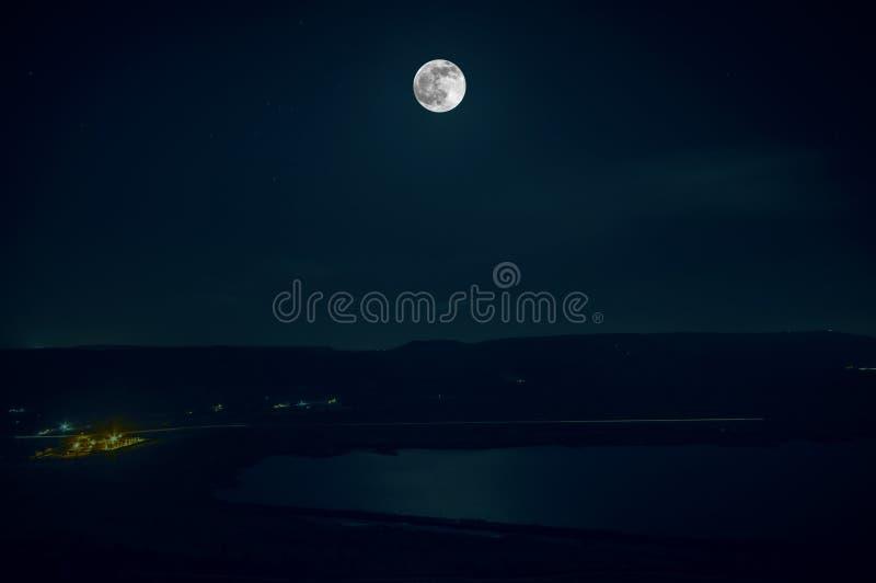 Colorful night landscape with lake, mountains, full moon, blue sky Khojasan Lake, Baku, Azerbaijan. Panoramic photo. Nature backgr royalty free stock photos