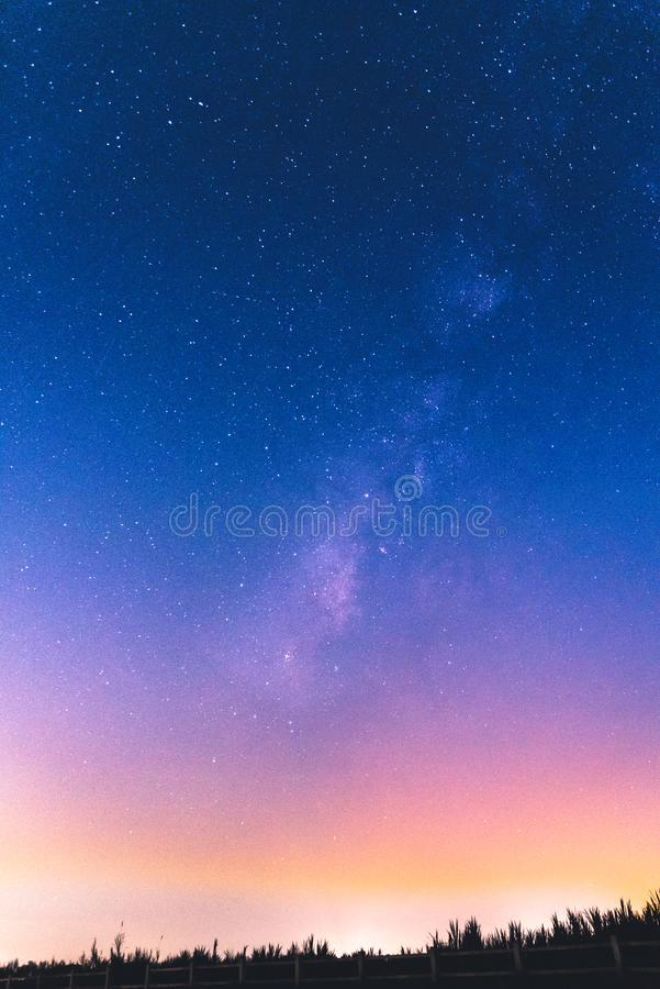 Colorful night sky with milky way. City-lit night sky with milky way stock photo
