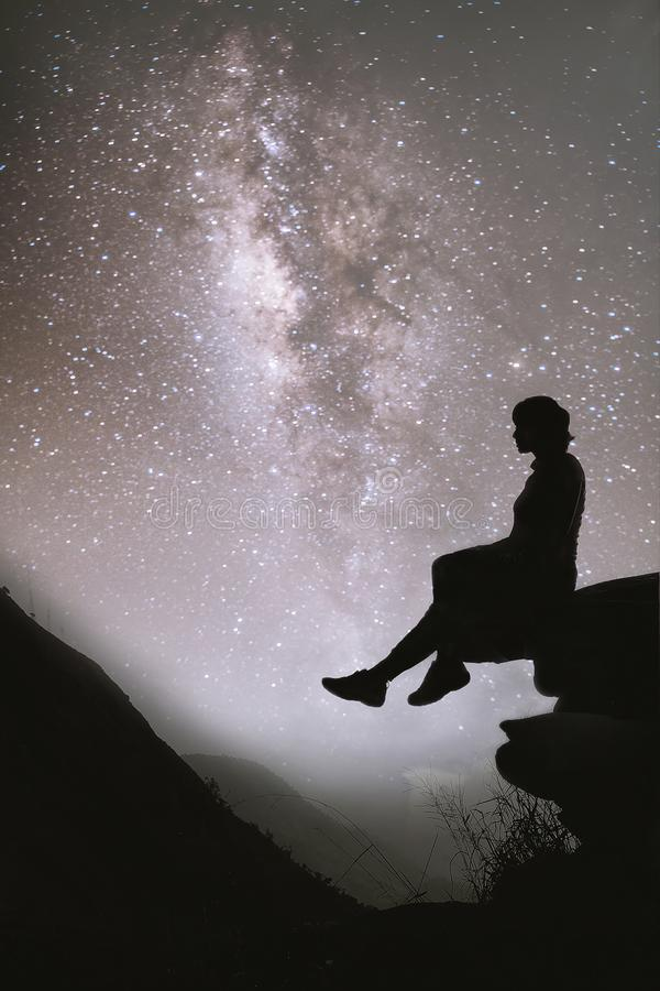 Colorful night sky with stars and silhouette of a standing girl sitting on the stone. Blue milky way with girl on the mountain. royalty free stock photo