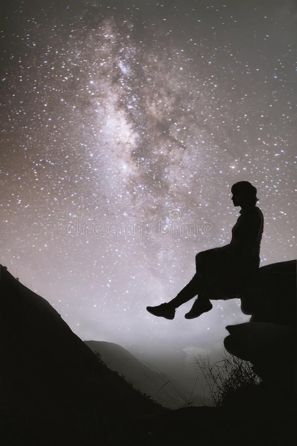 Colorful night sky with stars and silhouette of a standing girl sitting on the stone. Blue milky way with girl on the mountain. stock photography